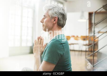 Ältere Menschen meditieren im Innenbereich - Stockfoto