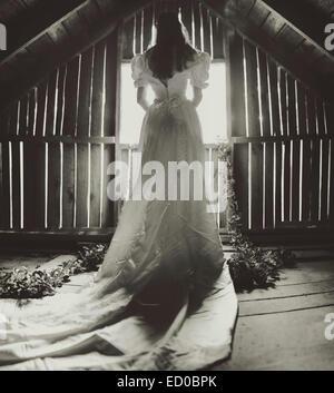 Rückansicht des junge Frau im Hochzeitskleid auf Dachboden - Stockfoto
