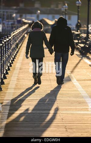 Die Pier in Swanage in Dorset. Ein paar gehen Hand in Hand bei Sonnenuntergang. - Stockfoto