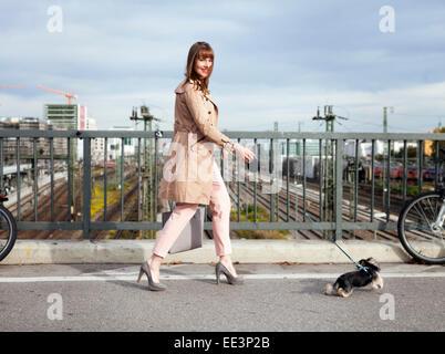 Junge Frau, Spaziergang mit dem Hund auf einer Brücke, München, Bayern, Deutschland - Stockfoto