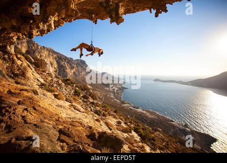 Weibliche Kletterer hängen am Seil nach erfolglosen Versuch nächste Haltegriff auf Klippe beim Schwierigkeitsklettern - Stockfoto