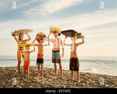Porträt der Familie mit drei Kindern (6-7, 10-11, 14-15) mit Surfbrettern am Strand, Laguna Beach, California, USA - Stockfoto
