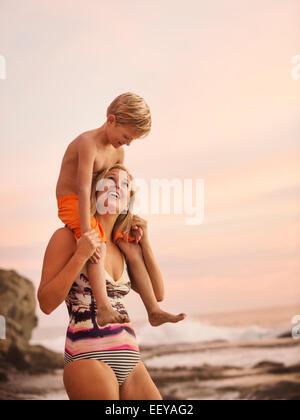 USA, California, Laguna Beach, Mutter mit Sohn (6-7) auf Schultern im freien - Stockfoto