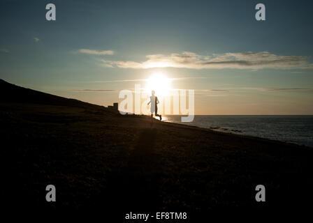 Silhouette der Mann läuft am Strand bei Sonnenuntergang, Galicien, Spanien - Stockfoto