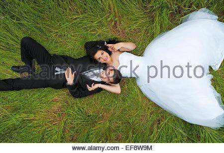 Braut und Bräutigam auf dem Rasen liegend - Stockfoto
