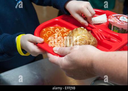 Ein kleines Kind an einer Grundschule in UK ist ein Schule-Dinner inklusive einer Jacke Kartoffel und Spaghetti - Stockfoto