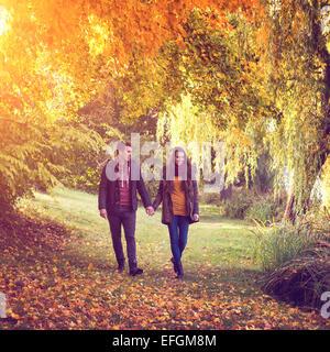 Paar Hand in Hand gehen in den Wald im Herbst - Stockfoto