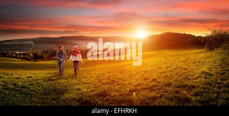 Liebendes Paar Hand in Hand laufen auf dem Feld. schöne Landschaft - Stockfoto
