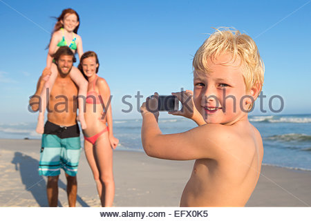 Junge, lächelnd in die Kamera, Aufnahme der Familie am Sonnenstrand - Stockfoto