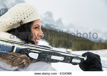 Lächelnde Frau hält Skier unter verschneiten Bergen - Stockfoto
