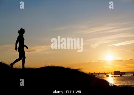 Gesamte Länge der Silhouette weibliche Läufer auf Hügel bei Sonnenuntergang - Stockfoto