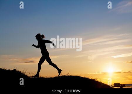Silhouette weibliche Läufer auf Hügel bei Sonnenuntergang - Stockfoto