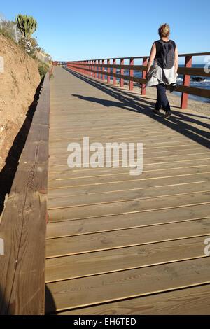 Frau zu Fuß auf Holzsteg, Strandpromenade verbindet Strände der Costa Del Sol, La Cala, Andalusien, Spanien. - Stockfoto