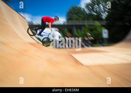 BMX-Biker Durchführung Tricks während der Fahrt auf einer Rampe - Stockfoto