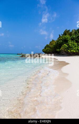 Ein Blick auf den Strand auf Makunudu Island auf den Malediven mit Sonnenliegen auf einem Steg in der Ferne - Stockfoto