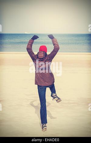 Retro-gefilterte Foto Frau springen auf Strand, Winter aktiven Lifestyle-Konzept. - Stockfoto