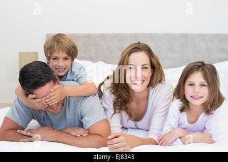 Glückliche Familie zusammen im Bett liegend - Stockfoto