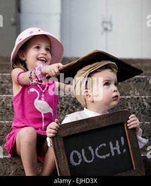 Freche Schwester trifft ihr Bruder über den Kopf mit Tafel - Stockfoto