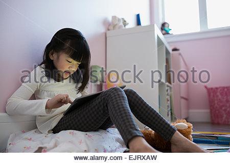Mädchen mit digital-Tablette im Schlafzimmer - Stockfoto