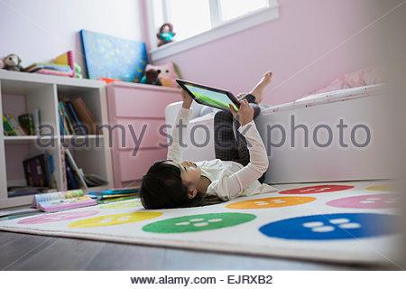 Mädchen mit digital-Tablette kopfüber im Schlafzimmer - Stockfoto
