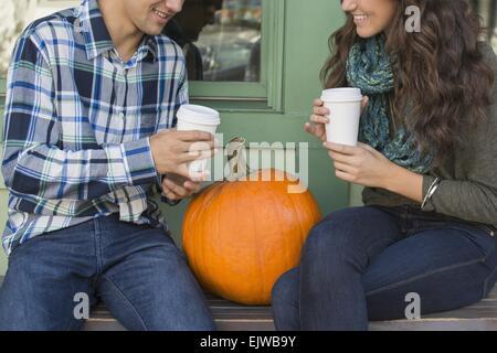 USA, Staat New York, New York City, Brooklyn, junges Paar sitzt auf der Bank mit Kaffeetassen - Stockfoto