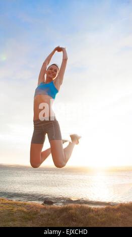 Frau springt mitten in der Luft am Strand, Low Angle view - Stockfoto