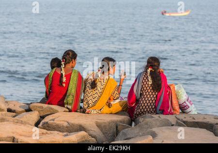 Bunt gekleidete Mädchen, gesellig Familie sitzen im Chat auf den felsigen Strand Küste bei Pondicherry oder Puducherry, - Stockfoto