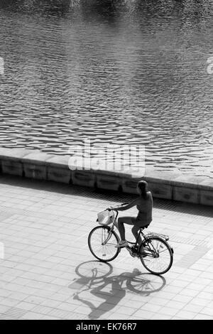 beleuchtete Silhouette des Mädchens mit dem Fahrrad, schwarz / weiß - Stockfoto