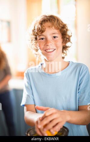 Teenager Entsaften Orange in Küche - Stockfoto