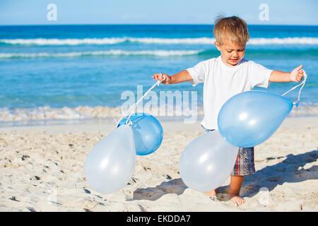 Junge spielt mit Ballons am Strand - Stockfoto