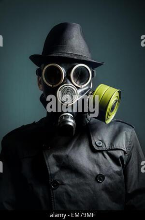 Mann in der Gasmaske, Regenmantel und schwarzen Hut auf dunklem Hintergrund - Stockfoto