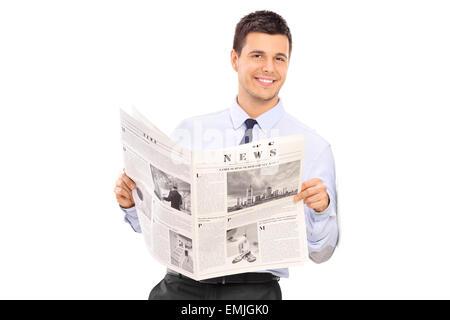 Gut aussehender Mann hält eine Zeitung und lehnte sich gegen eine Wand isoliert auf weißem Hintergrund - Stockfoto
