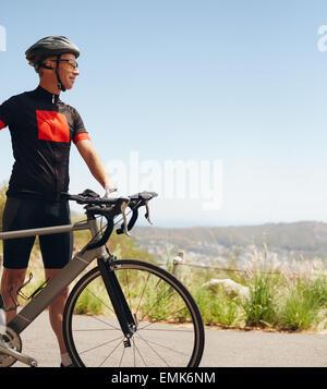 Bild des glücklichen männlichen Radfahrer mit seinem Fahrrad auf dem Lande. Junge Radfahrer mit seinem Fahrrad auf - Stockfoto