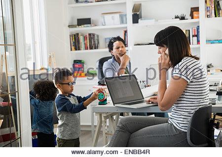 Eltern arbeiten im home-Office mit spielenden Kindern - Stockfoto