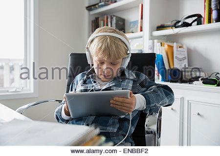 Jungen tragen von Kopfhörern und mit digital-Tablette - Stockfoto