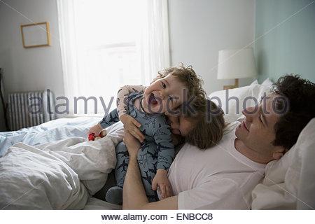 Vater und Kinder im Schlafanzug spielen im Bett - Stockfoto