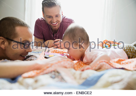 Homosexuelles Paar spielen mit Baby auf Bett - Stockfoto