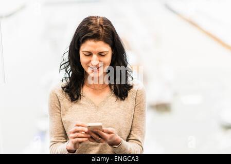 Eine Business-Frau sitzt an einem Fenster mit ihrem Smartphone. - Stockfoto