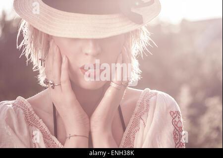 Outdoor-Porträt der jungen Frau, deren Gesicht durch einen Hut teilweise verdeckt wird - Stockfoto
