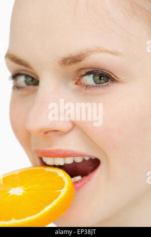 Nahaufnahme einer Frau eine Orangenscheibe in den Mund legen - Stockfoto