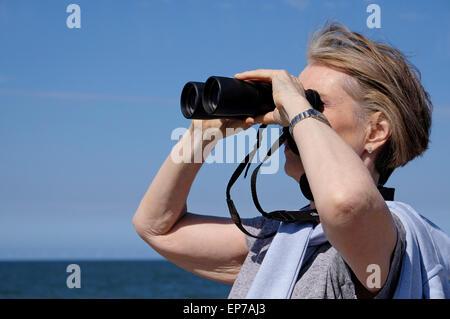 ältere Frau, die auf der Suche durch ein Fernglas - Stockfoto