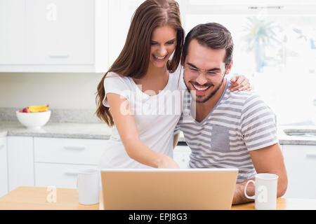 Junges Paar lächelnd und mit laptop - Stockfoto