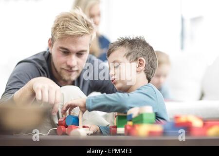 Vater und Sohn spielen mit Holzspielzeug - Stockfoto