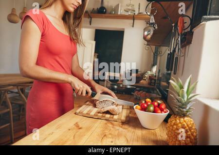 Aufnahme einer jungen Frau ein frisch gebackenes Brot auf einem heimischen Küchentisch schneiden beschnitten. Weibliche - Stockfoto