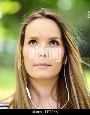Weibliche Studentin draußen im Park Musik über Kopfhörer hören - Stockfoto