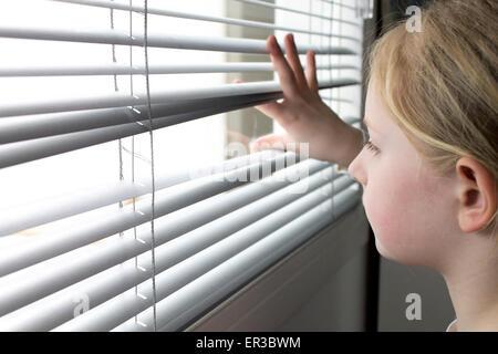 Mädchen auf der Suche durch Fenster-Vorhänge - Stockfoto