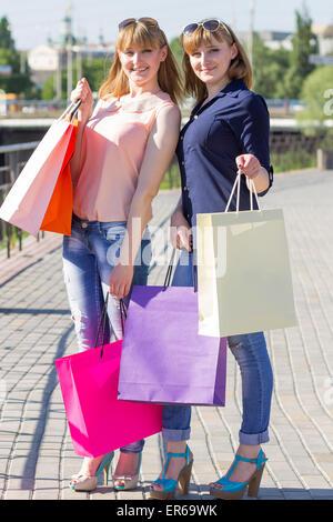 Junge Zwillinge Mädchen viel Spaß halten ihre Einkaufstüten. Zwei Frauen am Sommertag in der Stadt einkaufen - Stockfoto