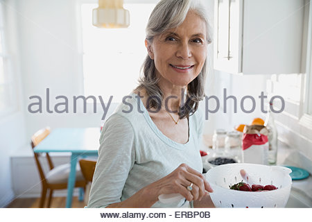 Porträt, lächelnde Frau waschen frischen Beeren in Küche - Stockfoto