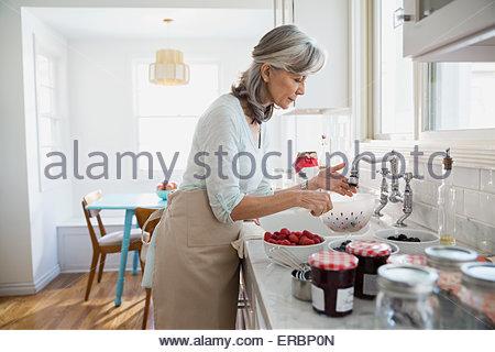 Frau machen Marmelade mit frischen Beeren in Küche - Stockfoto