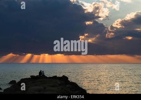 Dramatischer Himmel mit orange Sonnenstrahlen bis hinunter zum Wasser am Horizont aus Gewitterwolken; Paphos, Zypern - Stockfoto